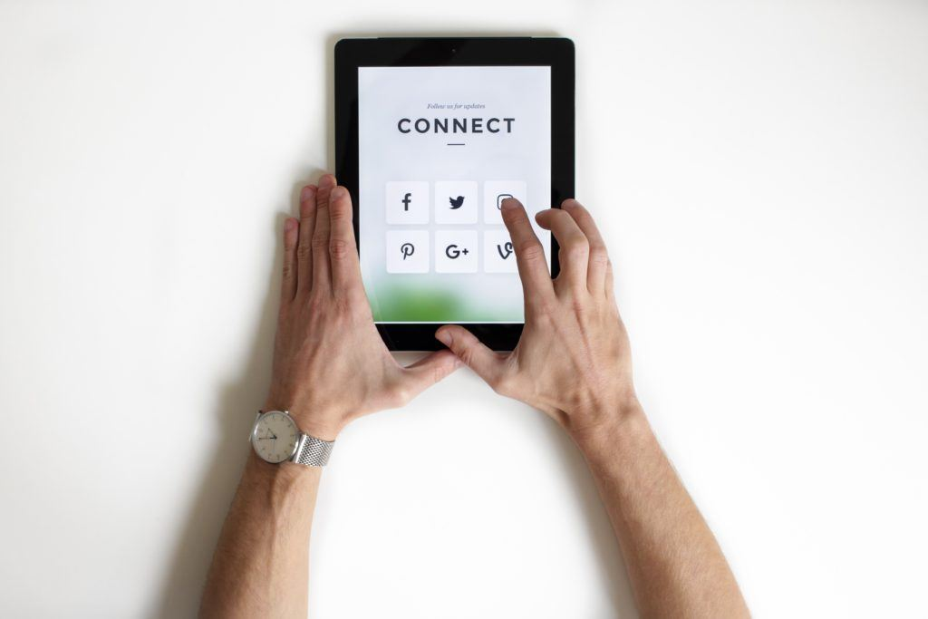 A man uses a tablet with the word 'connect' on, and social media icons